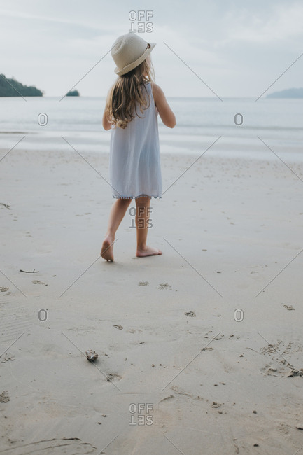 Young girl walking on a sandy beach