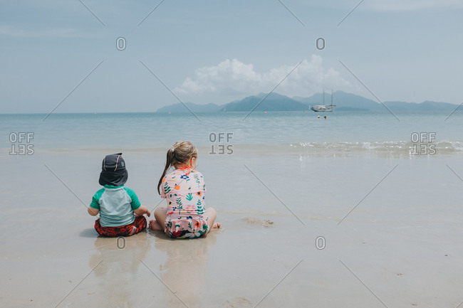 Two little kids sitting in the ocean tide