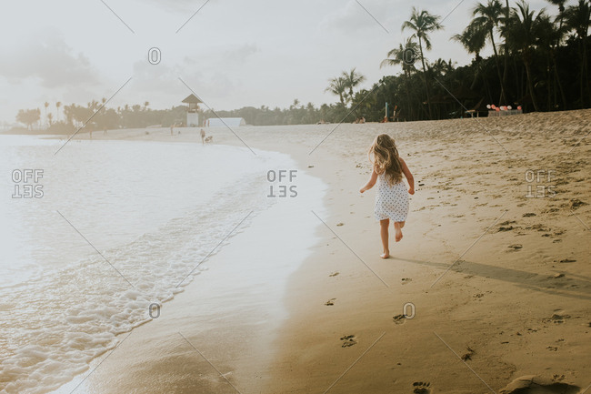 Young girl running on a sandy beach at sunset