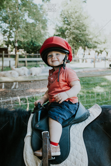 Toddler boy riding on a pony
