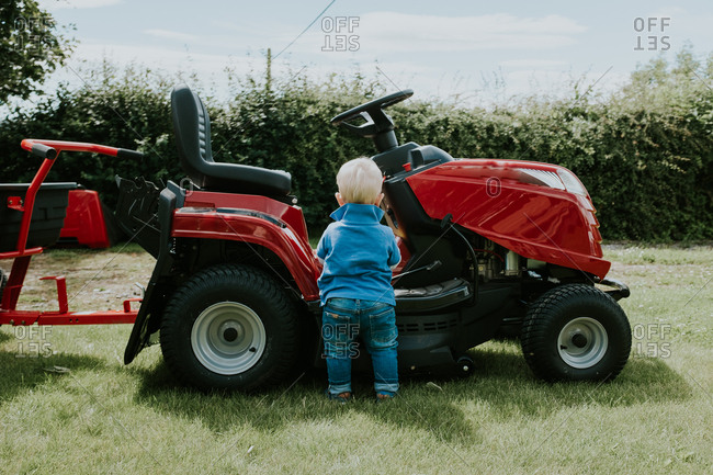 Rear view of blonde baby boy standing by lawn mower