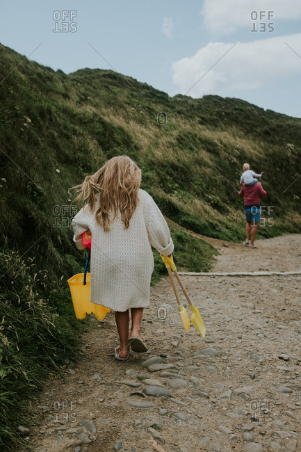 Father and children walking on beach path carrying shovels and buckets