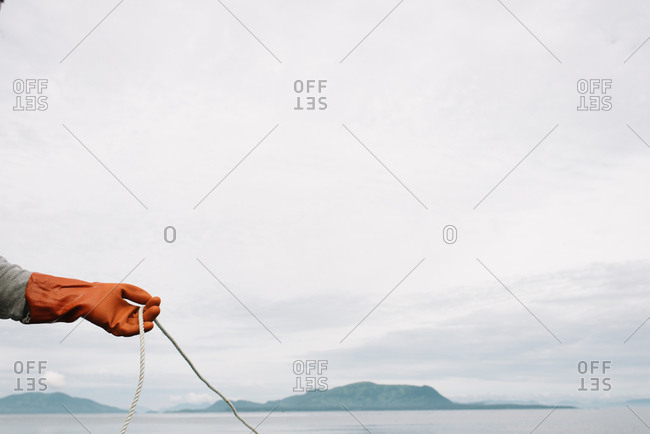 Hand wearing rubber glove holding a fishing rope line
