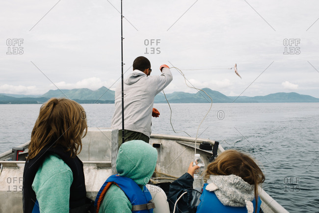 Children watching their father cast a rope into the water while deep water fishing