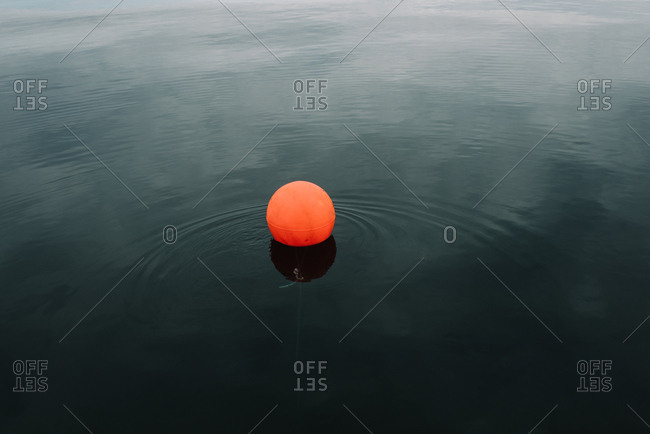 Orange fishing buoy in the water
