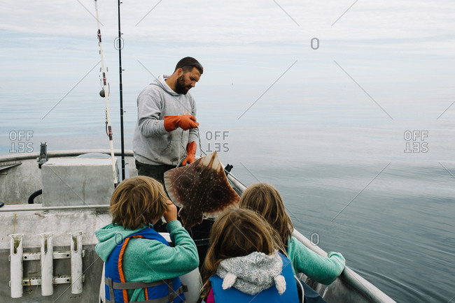 Children watch as father reels in a Big Skate