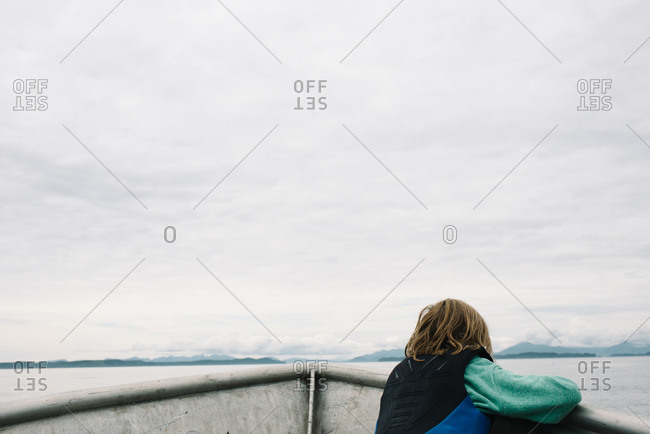Rear view of boy looking into the distance from a boat