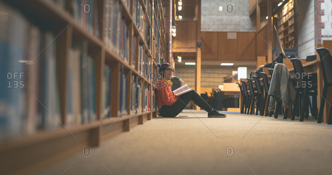 Thoughtful girl reading book in library