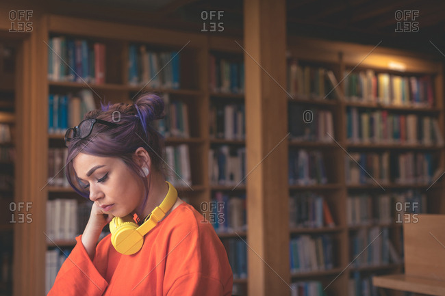 Thoughtful girl sitting in library