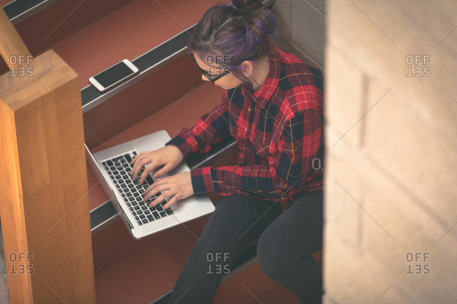 Girl using laptop in stairs