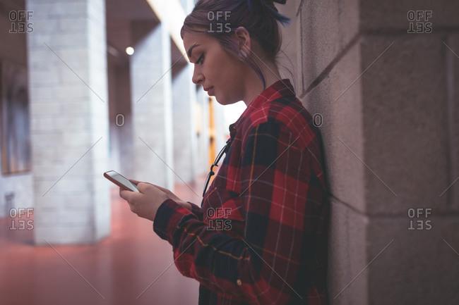 Girl using mobile phone in corridor