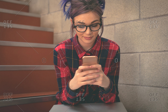 Girl using mobile phone in stairs