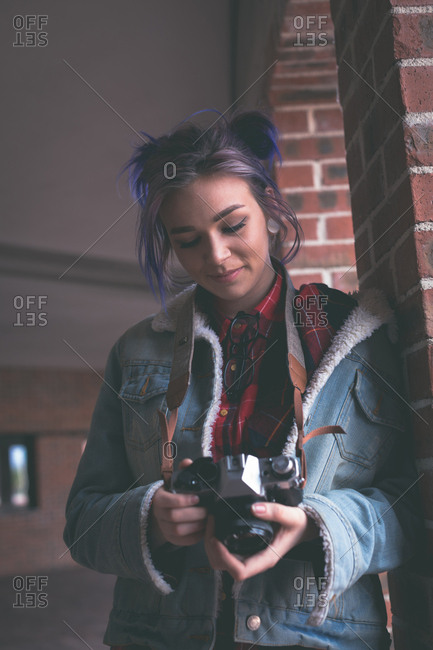 Girl standing with camera in corridor