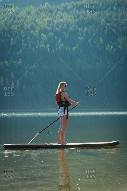 Woman doing stand up paddle boarding in river