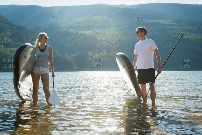 Couple with stand up paddleboard walking in river