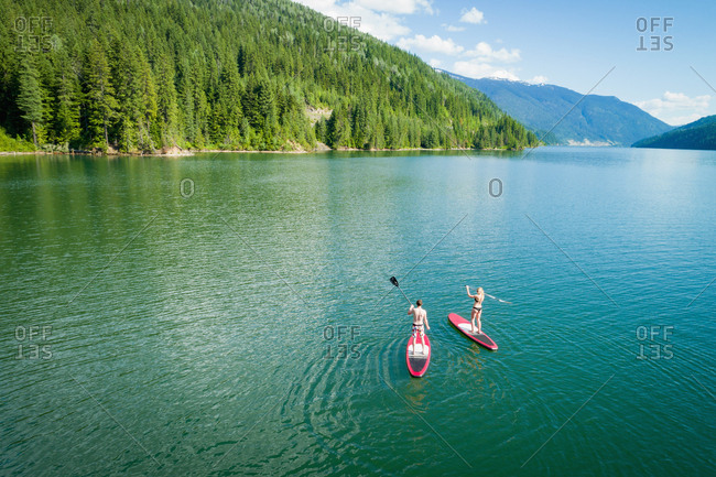 Couple doing stand up paddle boarding in river