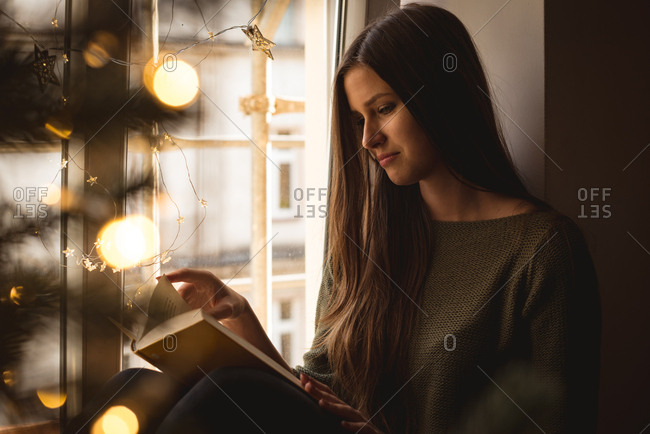 Woman reading novel at home during christmas