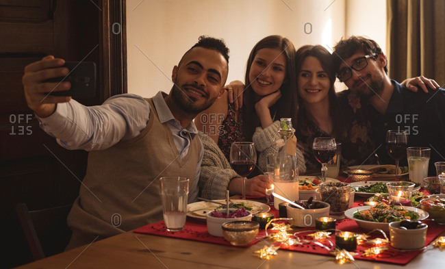Friends taking selfie with mobile phone while having meal during christmas