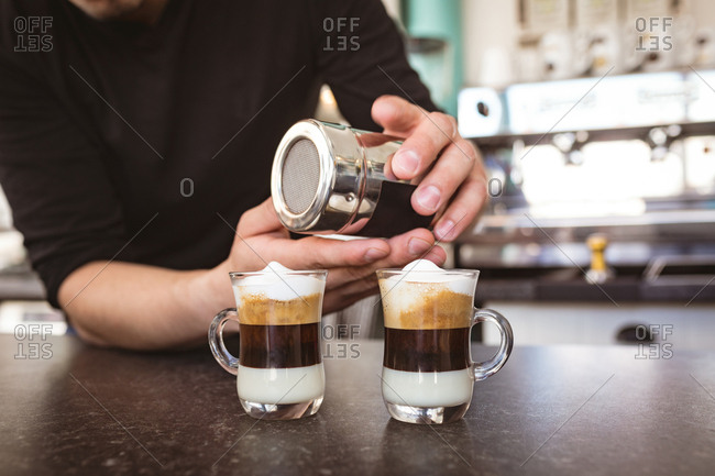 Man sprinkling coffee powder on coffee