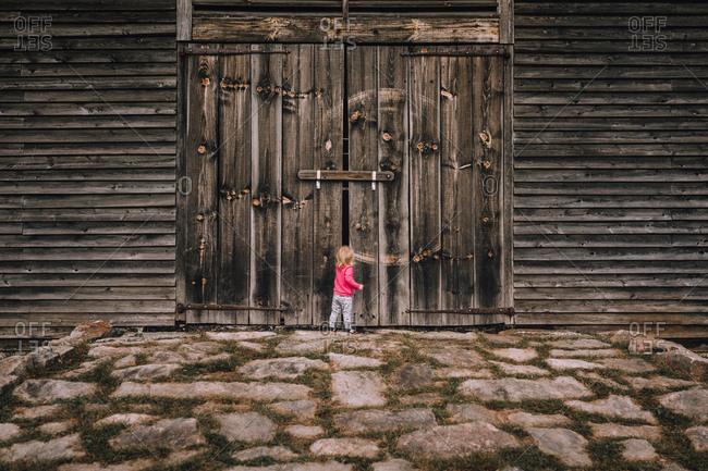 Little girl looking inside barn