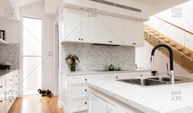 Country classic styled white kitchen with large gooseneck tap
