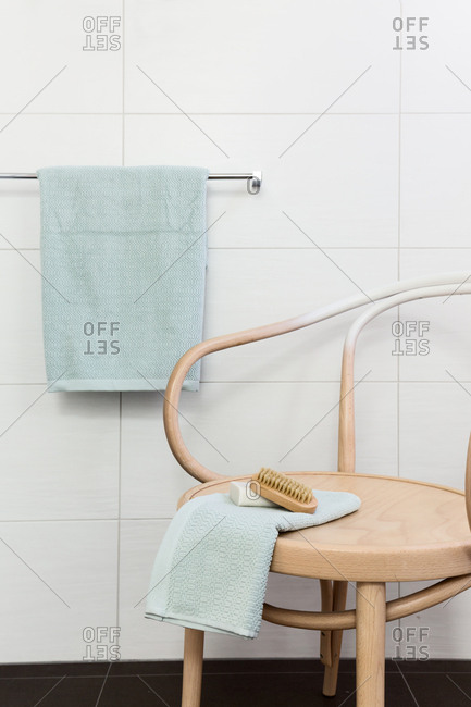 Bathroom decor details of wood chair towel and nail brush