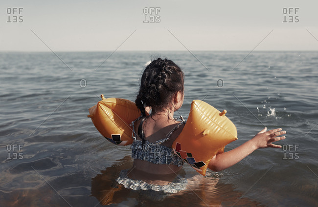 Girl swimming with inflatable armbands