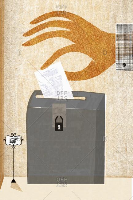 Hand putting ballot into ballot box