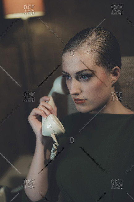 Retro 1960s woman on the phone while sitting in chair in hotel room at night.