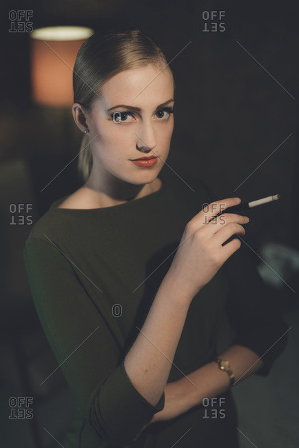 Retro woman in green dress standing with cigarette in hotel room at night.