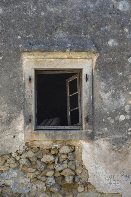 Antique wall with open window. Corfu, Greece.