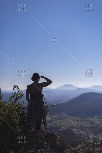 Silhouette of woman looking over hazy mountains. Corfu, Greece.