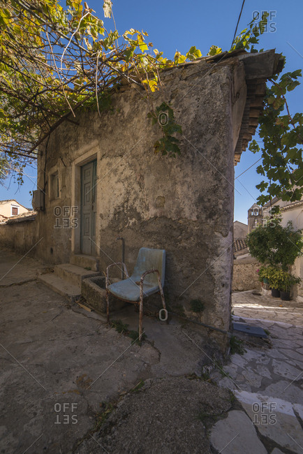 Old rusty chair outdoor in front of old dilapidated house. Doukades, Corfu, Greece.