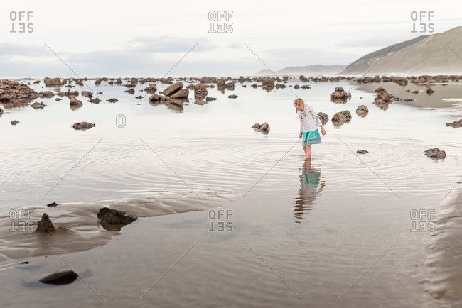Girl walking in high tide on a cloudy day