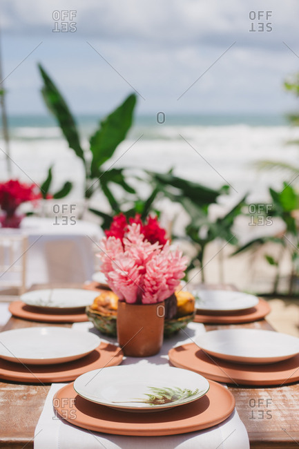 Table with place settings at reception for outdoor beach wedding