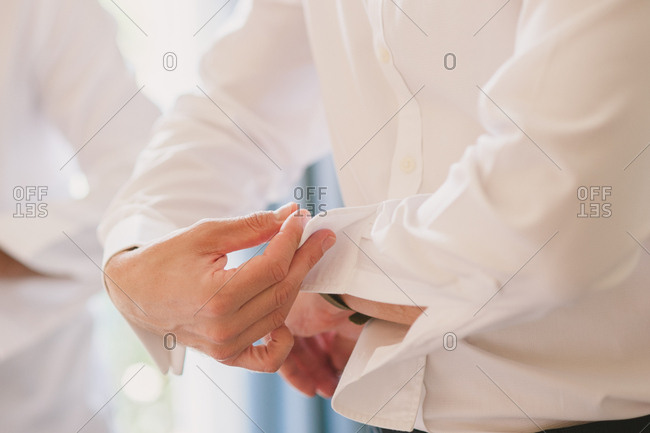 Groom adjusting the cuff of his dress shirt