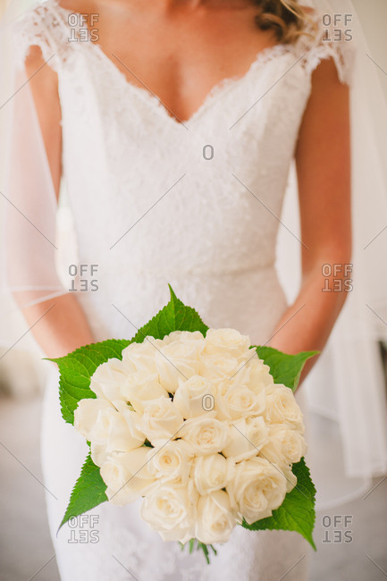Bride holding bouquet of white roses