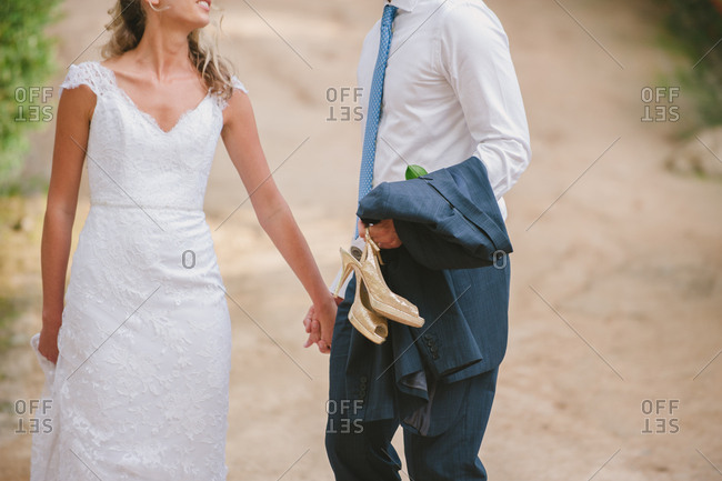 Groom carrying bride's shoes