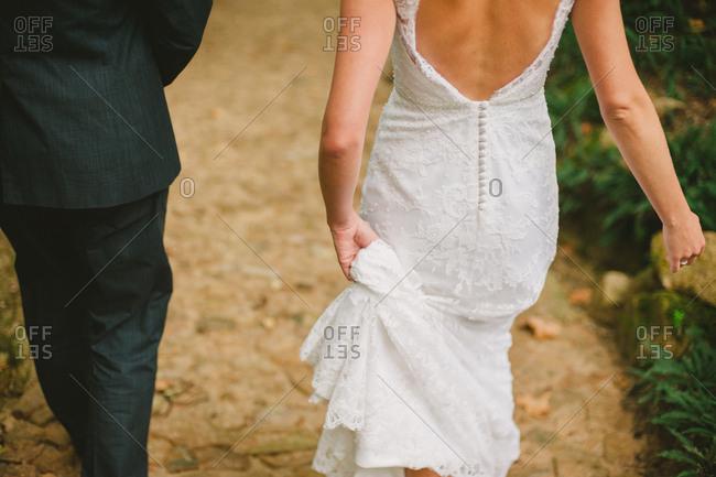 Bride holding edge of wedding dress while walking alongside groom