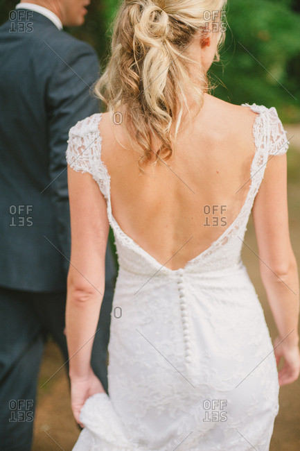 Back of bride in wedding dress walking with groom