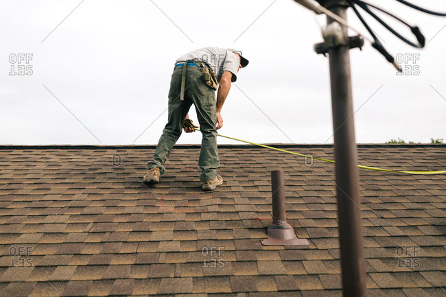 Man measuring a roof for solar panel installation