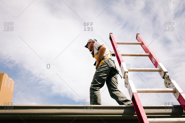 Low angle view of man walking on a roof