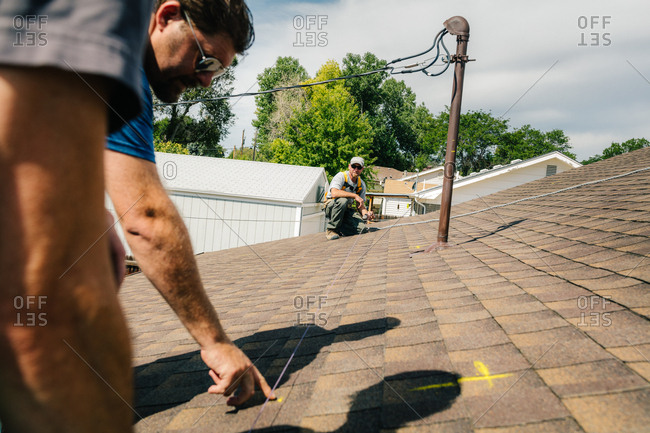Tradesman marking lines with a chalk line on a roof