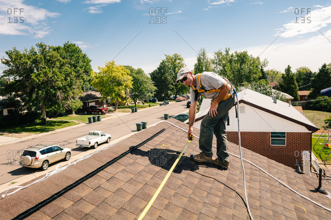 Man using a tape measure to measure for solar panel installation