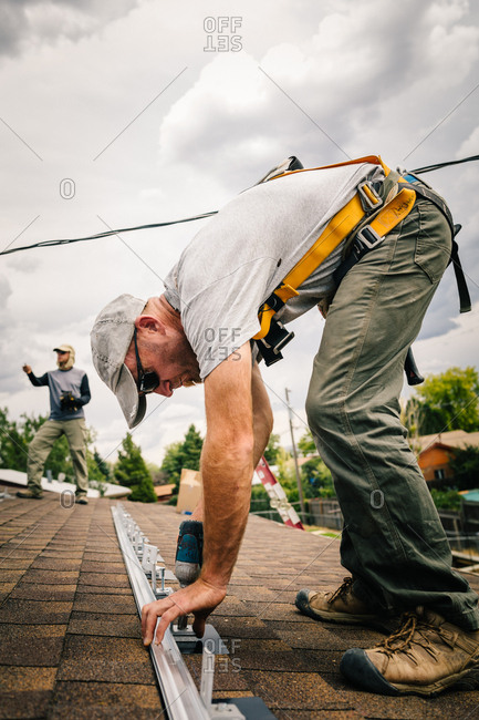 Workers installing brackets on a roof for solar panel installation