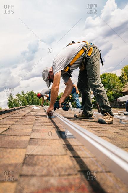 Men installing brackets on a roof for solar panel installation