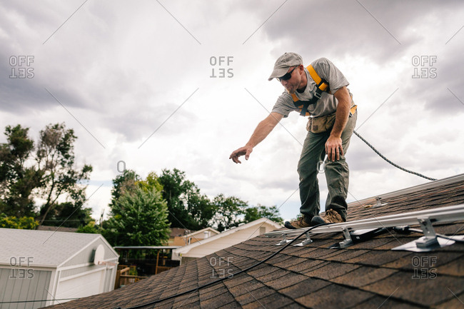 Construction worker on a roof installing brackets for solar panels