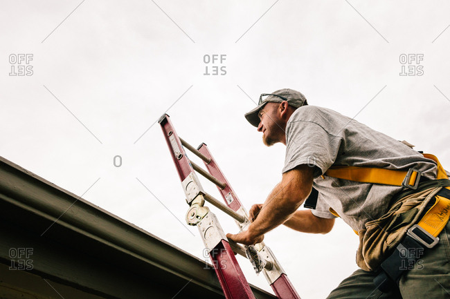 Low angle view of man climbing a ladder onto a roof