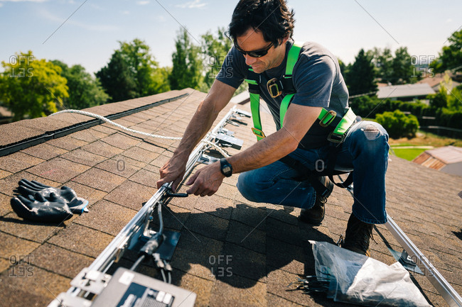 Tradesman installing components for solar panels on a roof