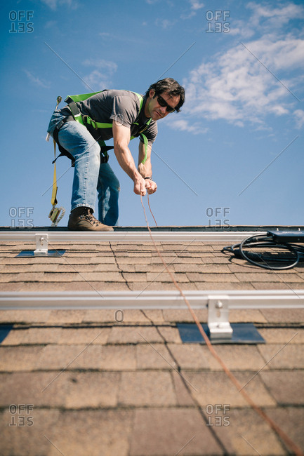 Low angle view of a man installing copper wires for solar panels on a roof